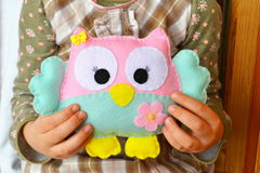 Little girl sits and holds an owl toy in the hands. Cute pink and blue felt toy. Home felt decor Royalty Free Stock Photos