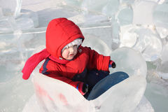 Little girl sits in ice nenuphar at winter Royalty Free Stock Photo