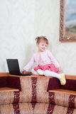 Little girl sits with a laptop Royalty Free Stock Images
