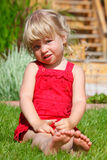 The little girl sits on a lawn Royalty Free Stock Images