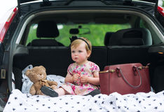 Little girl sits in luggage carrier of the family car. Royalty Free Stock Photo