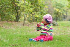 Little girl sits on a meadow and eats candy. Stock Photo