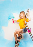 Little girl sits on a metal ladder Stock Photography
