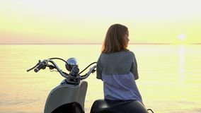 The little girl sits on the moped and watches a decline. On this video you can see as the close-knit family has a rest on the seashore. Children have amicably stock video