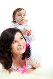 Little girl sits on mother which lying Stock Images
