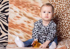 Little girl sits on a mottled striped couch. A child plays with a pyramid on the spotty background Royalty Free Stock Image