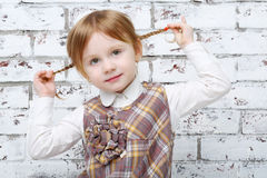 Little girl sits next to brick white wall Royalty Free Stock Photo