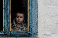 A little girl sits in an old hut on a window on which the paint faded royalty free stock images