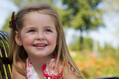 A little girl sits on a park bench Stock Photo