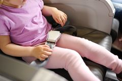 The little girl sits in a passenger chair of the plane stock photo