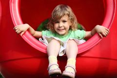Little girl sits in plastic hole on playground Stock Photo