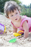 Little girl sits and plays on the beach Stock Photography