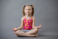 The little girl sits in a pose meditation. At the studio Stock Photography