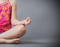 The little girl sits in a pose meditation Royalty Free Stock Image