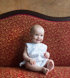 The little girl sits on a red sofa. stock photos