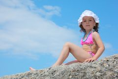 Little girl sits on rock against sky Royalty Free Stock Images