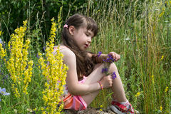Little girl sits on a rock and looks at a flower Royalty Free Stock Photography