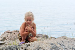 Little girl sits on rocks next to sea Stock Photography