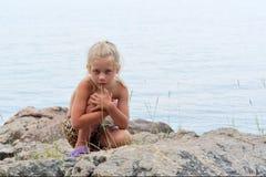 Little girl sits on rocks next to sea. Shot in the Cape Aia Nature Reserve, near Balaklava/Sevastopol, Crimea peninsula, Black Sea, Ukraine Stock Photography