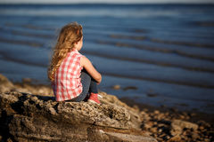 Little girl sits on a rocky shore and looks at the sea. Stock Image