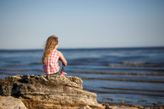 Little girl sits on a rocky shore and looks at the sea. Stock Photos