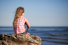 Little girl sits on a rocky shore and looks at the sea. Stock Photography