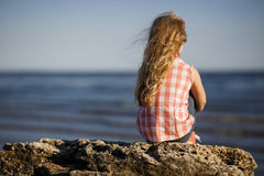 Little girl sits on a rocky shore and looks at the sea. Stock Images