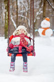 Little girl sits on seat suspended on chains in winter park, Stock Photography