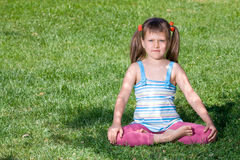 Little girl sits in the shade in asana on grass Royalty Free Stock Photo