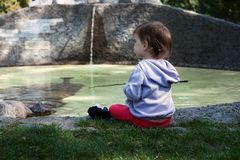 The little girl sits on the shore of the pond royalty free stock photos