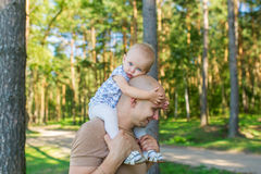 Little girl sits on shoulder at father in park in autumn Royalty Free Stock Images