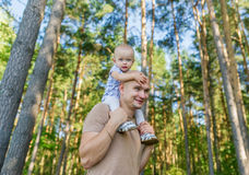 Little girl sits on shoulder at father in park in autumn stock photography