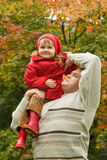 Little girl sits on shoulder at man In park Stock Photos