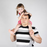 Little girl sits on shoulders of father and looks down Stock Photo