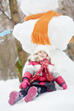 Little girl sits on snow in front of big snowman Stock Image
