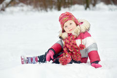 Little girl sits on snow in park Stock Photo