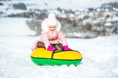 Little girl sits on snow tube royalty free stock photography