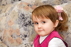 Little girl sits on a sofa in cosy room Stock Image