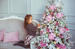 Little girl sits on a sofa and touches a tree toys on in Christmas tree at home Royalty Free Stock Photography