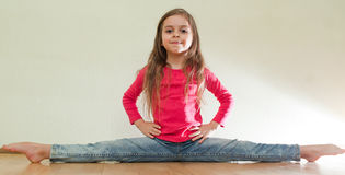 Little girl sits on a splits Royalty Free Stock Images