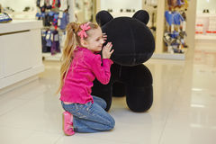 Little girl sits squatted and sqeezing up to stuffed toy Stock Photography