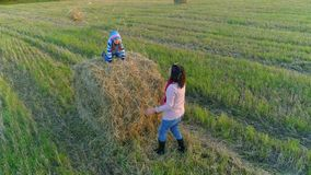 Little girl sits on the stack and throw straws to her mom. Little girl sits on the stack and throw straws to her mom on the rustic field at the countryside in stock video footage