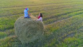 Little girl sits on the stack and throw straws to her mom. Little girl sits on the stack and throw straws to her mom on the rustic field at the countryside in stock video