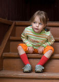 Little girl sits on a stairs looks toward Royalty Free Stock Images