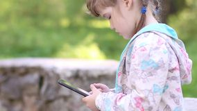 Little girl sits on stone wall and plays with tablet PC stock video footage