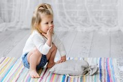 A little girl sits on a striped, colorful carpet. She is impressed with the present. It lies in front of her in a bag stock photo