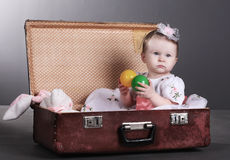 Little girl sits in a suitcase Royalty Free Stock Photo