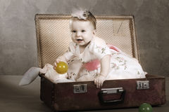 Little girl sits in a suitcase Stock Photo