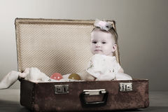 Little girl sits in a suitcase. Stock Photos