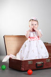 Little girl sits in a suitcase Royalty Free Stock Image